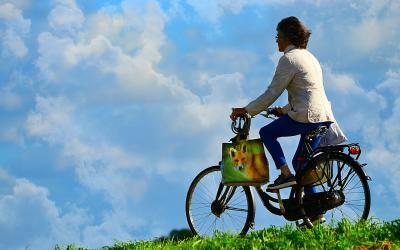 A woman riding a bike on a green hill. A bright blue sky with patchy white clouds is in the background.