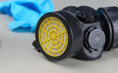 a black and yellow respirator mask with blue protective gloves in the background.