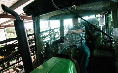 Farmer sitting inside the cab of a green tractor parked inside a machine shed.