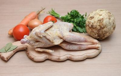 An uncooked, seasoned whole chicken on a cutting board with fresh vegetables.
