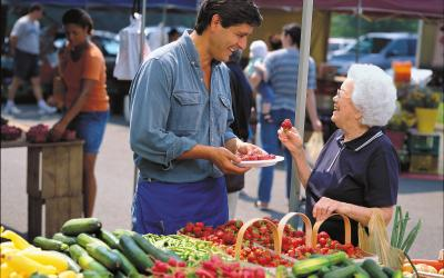 A male vendor serving a strawberry sample to an older woman at a farmers market stand.