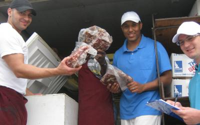 Three men inspecting meat from a freezer at an outdoor market.