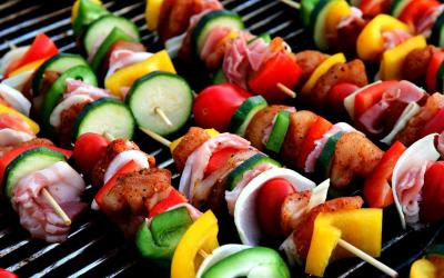 Several kabobs with pieces of fresh vegetables and lean meats cooking on a grill.