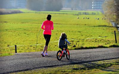 A mother jogging down a paved country trail next to a child riding an orange bicycle.