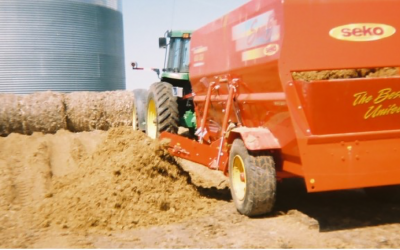 A green tractor pulling a red wagon next to a pile of wet distillers grains.