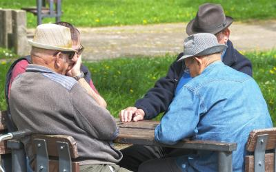 Group of men playing a board game outside.