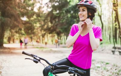 Woman in pink shirt buckling helmet under her chin