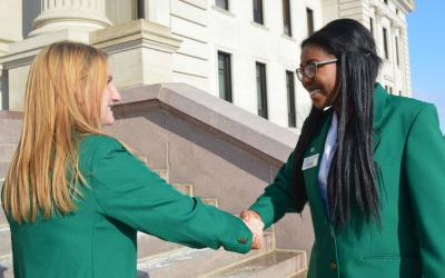 two ladies in green jackets shake hands in front of a building.