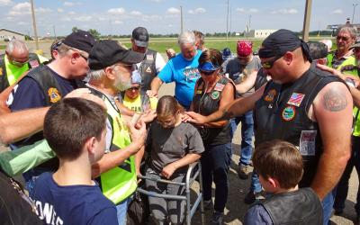 Jackie Rhode and members of the Christian Motorcyclist Association huddling for a group prayer.