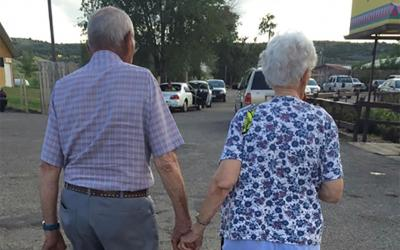 Two older people holding hands while walking.