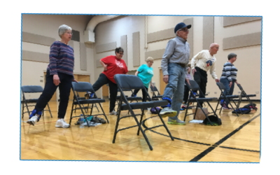 a group of older adults starting to exercise while standing behind folding chairs