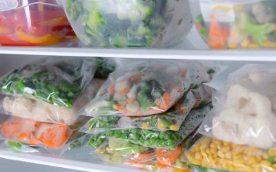 Plastic bags and containers with frozen vegetables in refrigerator