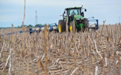 A green tractor planting seeds in a no-till field. Courtesy: United Soybean Board [CC BY 2.0] via Flickr