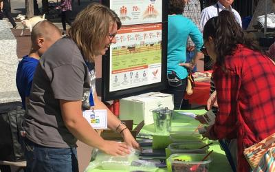Woman at a booth demonstrating beef sustainability.