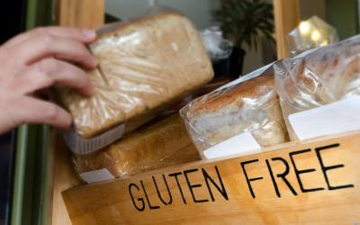 "A hand grabbing a loaf of bread from a shelf labeled ""gluten-free"""