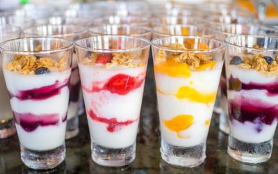 A variety of ruit, yogurt, and granola parfaits arranged on a counter.