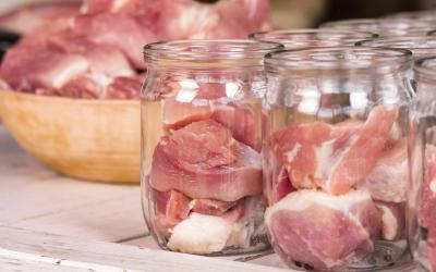 A bowl of raw meat being distributed into clear, glass jars.