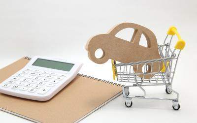 A wooden car cutout placed inside a small shopping cart next to a calculator and a notebook.