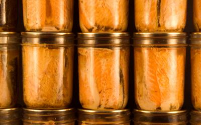Several jars of canned salmon filets stacked neatly on top of each other.