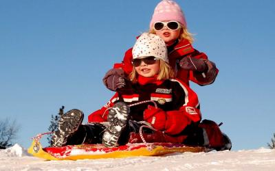 Two young girls in winter clothing riding on a sled.