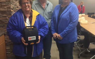 an image of two women and a man with a donated automated external defibrillator