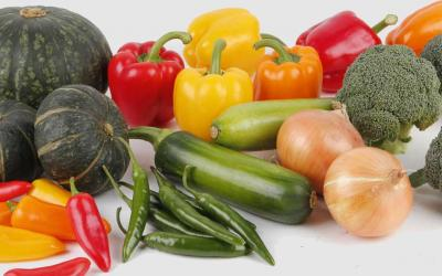 A variety of fresh vegetables displayed on a white countertop.