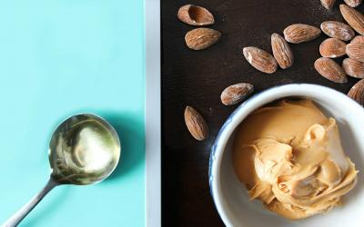 Almonds, a tablespoon of oil, and almond butter sitting on a countertop