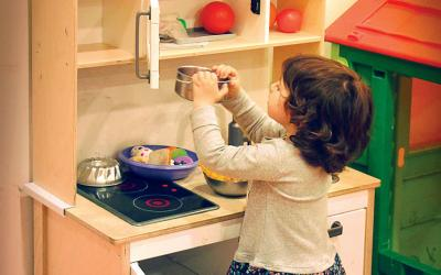 Young girl pretending to cook in a children's play kitchen.
