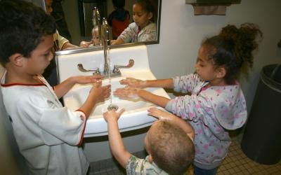 Three children washing their hands together in a bathroom sink.