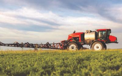 A red sprayer in a green field with a cloudy sky in the background.