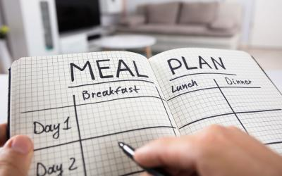 Hands holding a notebook with a meal planning grid drawn out. The grid has sections for breakfast, lunch and dinner across several days.