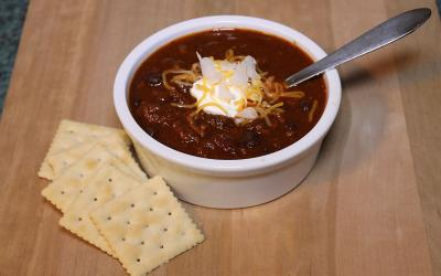 A bowl of chili topped with sour cream, onions, and cheese with saltine crackers on the side.