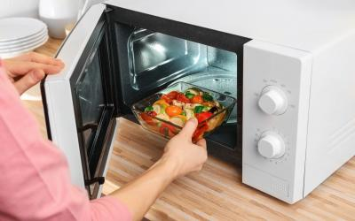 Woman putting bowl with vegetables in microwave oven.