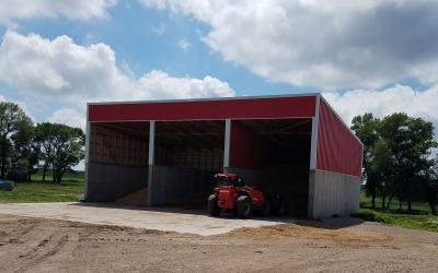 A red, three-stall feed shed with a dwindling supply of livestock feed.