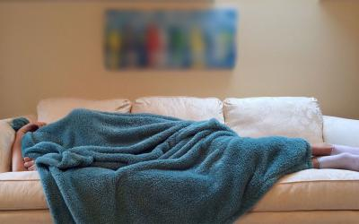 A person sleeping under a blue blanket on a white.