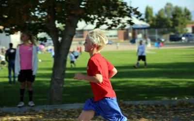 a young boy in a red shirt running
