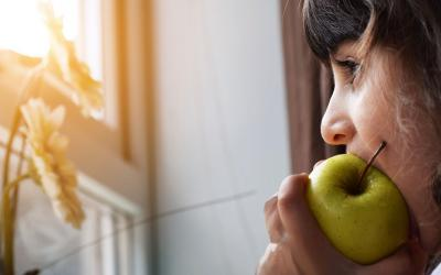 A young woman eating a green apple while watching the sun rise outside her window.