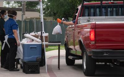 A man in a pickup truck picking up a bag of farmers market food at a pickup table being serviced by two women in personal protective gear.