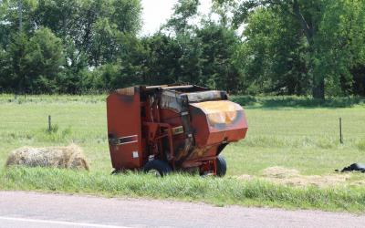 A red, round hay baler that has been burned up from a fire.