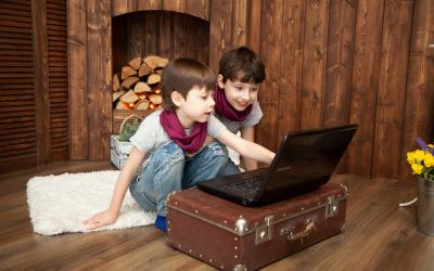 Two children sitting on the floor in front of a laptop. One of the children is pointing at the computer screen.