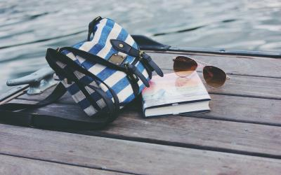 a book, sunglasses, and bag sitting on a dock by the water.