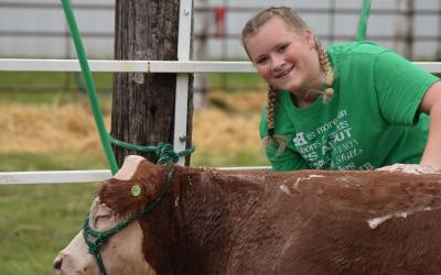 Ellie Wagner posing next to a cow at the Yankton County Fair.