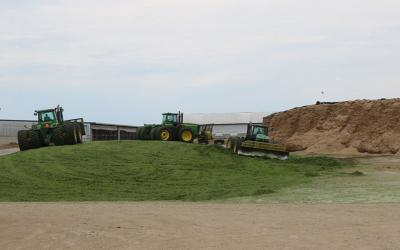 Three John Deere Tractors moving silage and packing the corn silage to make a drive over silage pile.
