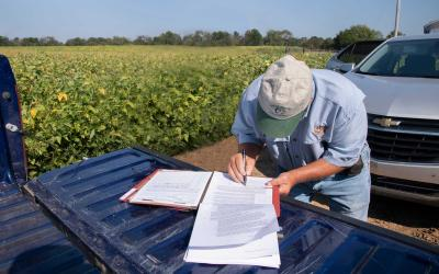 Farmer signing a lease on the tailgate of a pickup.