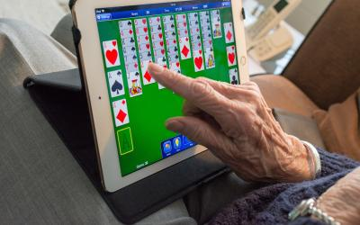 an older adult playing solitaire on an iPad
