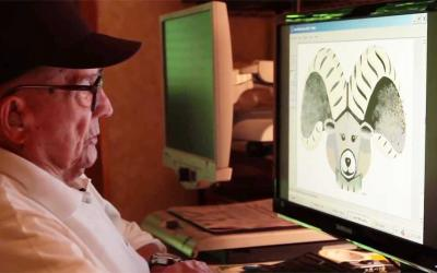 An older male adult composing an illustration on a computer screen.