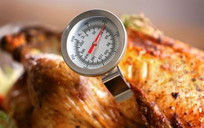 A golden, roast turkey with a food thermometer in it.