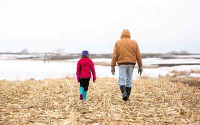 Young girl and grandfather walking through cornfiled stuble in winter.