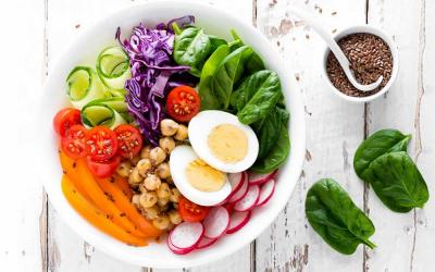 A salad bowl filled with a variety of fresh vegetables and slived eggs.