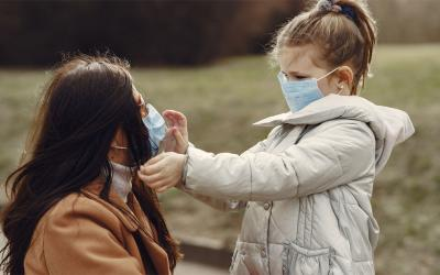 Mother and young daughter wearing masks in an outdoor park.